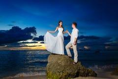 Jeunes mariés sur une plage tropicale avec le coucher du soleil dans le backg Image libre de droits