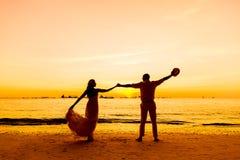 Jeunes mariés sur une plage tropicale avec le coucher du soleil dans le backg Photo stock