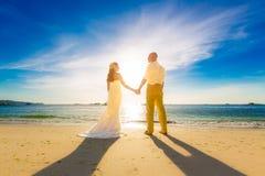 Jeunes mariés sur une plage tropicale avec le coucher du soleil dans le backg Photographie stock libre de droits