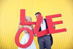Jeunes mariés tenant de grandes lettres d'amour Photographie stock