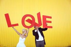 Jeunes mariés tenant de grandes lettres d'amour Image libre de droits