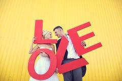 Jeunes mariés tenant de grandes lettres d'amour Photo stock