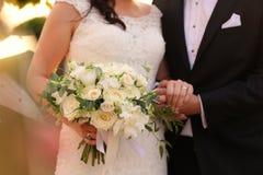 Jeunes mariés tenant des mains avec le bouquet nuptiale Photo stock