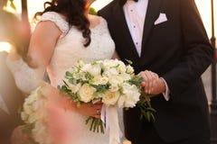 Jeunes mariés tenant des mains avec le bouquet nuptiale Image stock