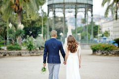 Jeunes mariés tenant des mains dans le jardin public de Naples, Italie Images libres de droits