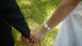 Jeunes mariés tenant des mains dans le jour d'été banque de vidéos