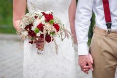Jeunes mariés tenant des mains dehors image stock