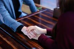 Jeunes mariés tenant des mains discutant épouser et lune de miel i Photographie stock