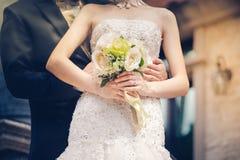 Jeunes mariés tenant des mains et un bouquet des fleurs comme toke Images libres de droits