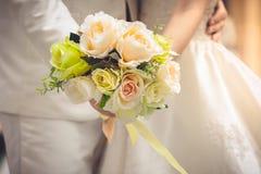 Jeunes mariés tenant des mains et un bouquet des fleurs comme toke Image stock