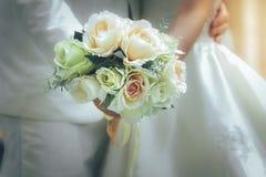 Jeunes mariés tenant des mains et un bouquet des fleurs comme toke Photographie stock libre de droits