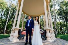 Jeunes mariés tenant des mains près de la tonnelle en parc Couples de mariage dans l'amour au jour du mariage Image libre de droits