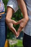 Jeunes mariés tenant des mains sous forme de coeur photo libre de droits