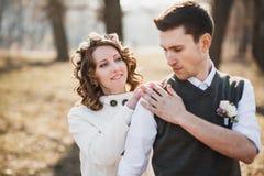 Jeunes mariés tenant ensemble au printemps le parc Image libre de droits