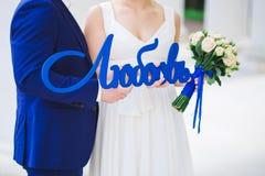 Jeunes mariés tenant l'amour de mot Photographie stock