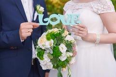 Jeunes mariés tenant l'amour en bois de mot Photos stock
