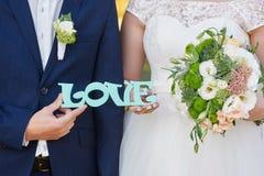Jeunes mariés tenant l'amour en bois de mot Photo stock