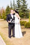 Jeunes mariés tenant le bouquet et l'amour en bois de mot Photographie stock