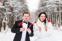 Jeunes mariés tenant les coeurs de papier en parc d'hiver Image stock
