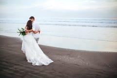 Jeunes mari?s magnifiques ?l?gants marchant sur la plage d'oc?an pendant le temps de coucher du soleil photos libres de droits