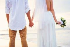 Jeunes mariés, ménage marié nouvellement romantique tenant des mains, Ju Photographie stock
