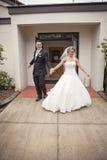 Jeunes mariés quittant l'église Photos stock