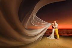 Jeunes mariés sur une plage tropicale avec le coucher du soleil dans le backg Image stock