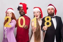 Jeunes meilleurs amis adultes de plan rapproché montrant le numéro 2018 à l'appareil-photo Photos stock