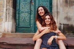 Jeunes meilleurs amis féminins s'asseyant sur des escaliers et étreindre Filles heureuses riant et ayant l'amusement Images libres de droits
