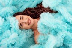Jeunes mensonges attrayants de femme de brune enveloppés dans un nuage pelucheux de sa robe bleue photographie stock libre de droits