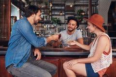 Jeunes modernes dans le café ayant des boissons Photo stock