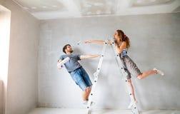 Jeunes murs de peinture de couples dans leur nouvelle maison Images libres de droits