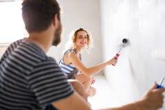 Jeunes murs de peinture de couples dans leur nouvelle maison Images stock