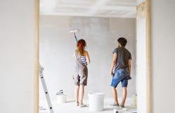 Jeunes murs de peinture de couples dans leur nouvelle maison Photographie stock