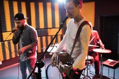 Jeunes musiciens chantant dans le studio record photographie stock libre de droits