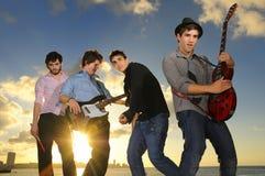 Jeunes musiciens mâles avec des instruments au coucher du soleil Photographie stock libre de droits