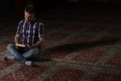Jeunes musulmans Guy Reading The Koran Photos libres de droits
