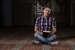 Jeunes musulmans Guy Reading The Koran Image libre de droits