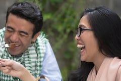 Jeunes musulmans heureux mangeant de la nourriture riant et souriant extérieur Photographie stock