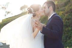 Jeunes nouveaux mariés romantiques embrassant au jardin Photos stock