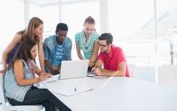 Jeunes occasionnels à l'aide de l'ordinateur portable dans le bureau Photographie stock libre de droits