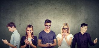 Jeunes occasionnels à l'aide du téléphone portable se tenant ensemble contre le mur en béton image libre de droits