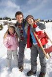 Jeunes père et enfants dans la neige avec le traîneau Photographie stock libre de droits