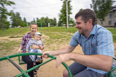 Jeunes père et mère avec le fils 1 3 ans montant sur le carrousel Images stock