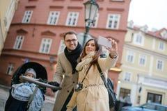 Jeunes père et mère avec le fils dans la poussette de bébé dehors Photo stock