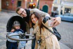 Jeunes père et mère avec le fils dans la poussette de bébé dehors Photo libre de droits
