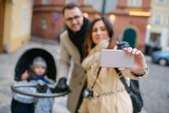 Jeunes père et mère avec le fils dans la poussette de bébé dehors Photographie stock