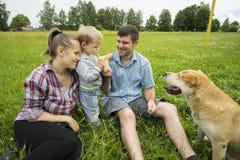 Jeunes père, mère et fils 1 3 ans, chien sur la pelouse verte lait de consommation de garçon Image stock