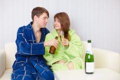 Jeunes paires à la maison sur le divan avec de la bière et le vin Photographie stock libre de droits
