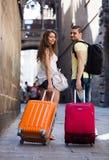 Jeunes paires avec le bagage marchant par la ville Photographie stock libre de droits